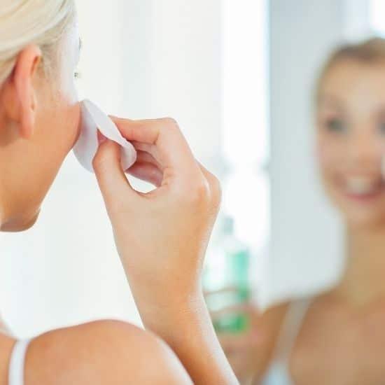 Kasvojen puhdistusta peilin edessä vanulapulla