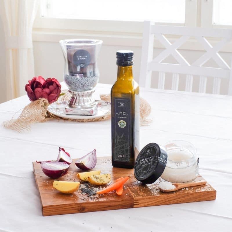Saaren Taika cuisine extra virgin oliiviöljy ja sormisuola aseteltuna Saaren Taika cuisine leikkuulaudalle leikattujen kasvisten kanssa