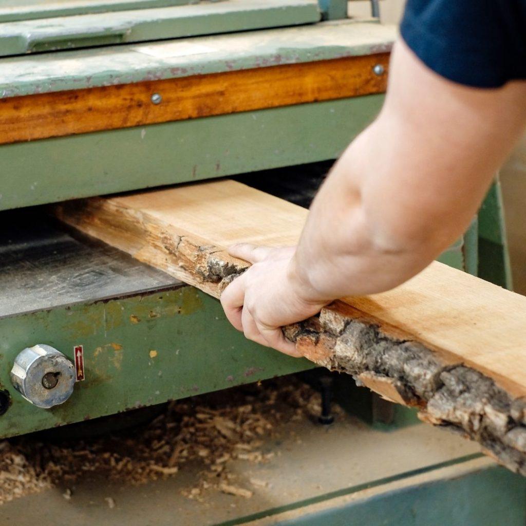 puuseppä höylää tammilankkua