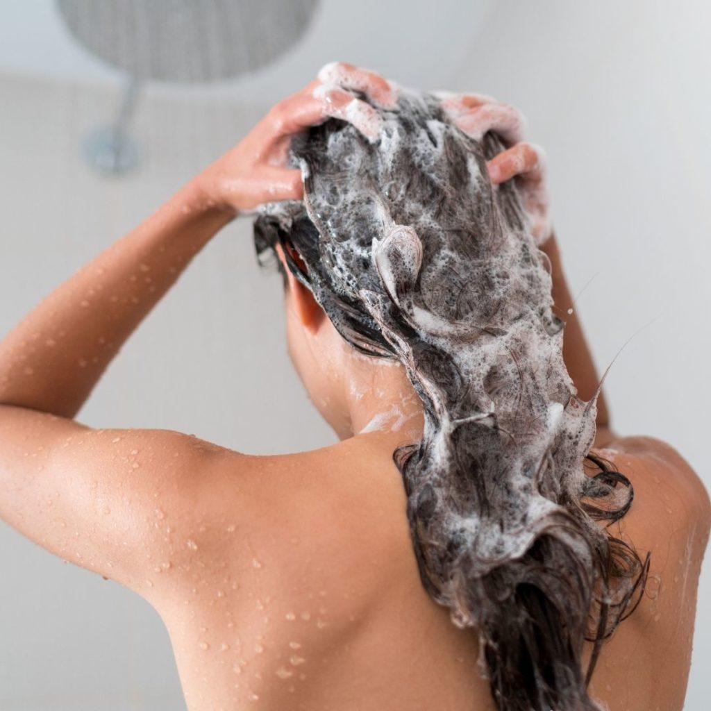 Huuhtelee päänahkaa suihkun alla